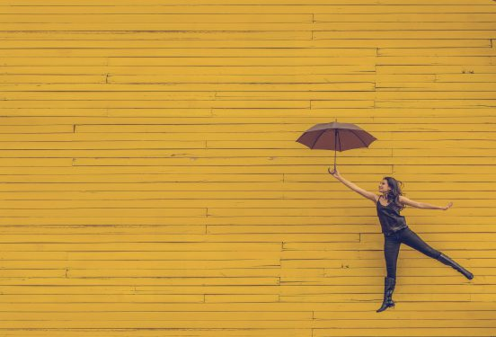 Women with umbrella with yellow background