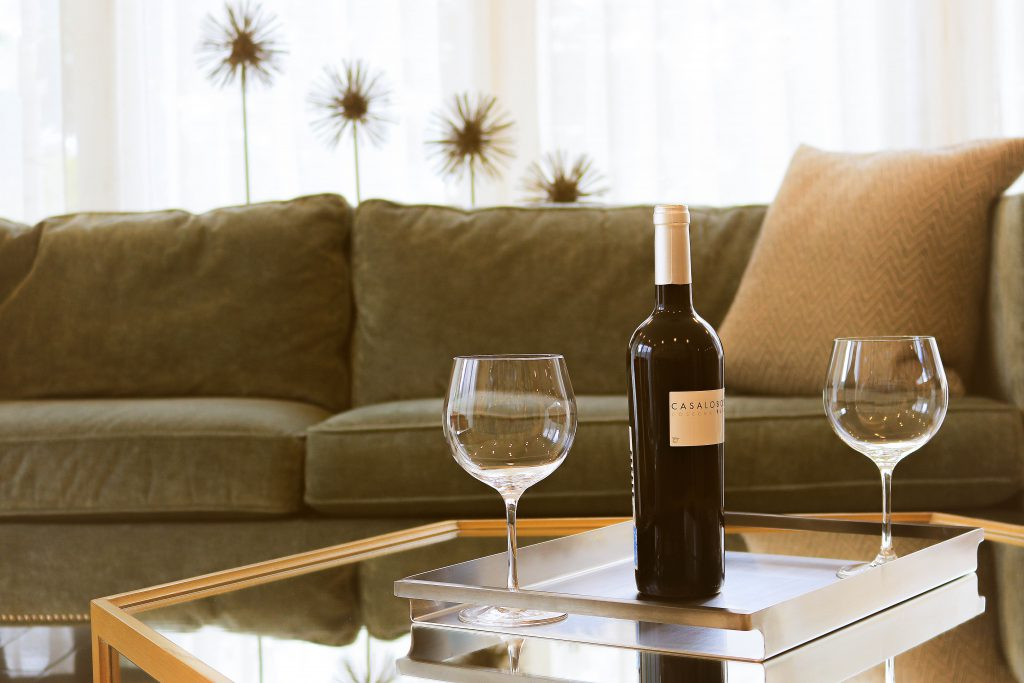 wine bottle and two glasses on top of a coffee table in an airbnb apartement managed by guestready